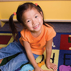 A stock photo of a pre-school aged girl with pigtails sitting on a colourful mat