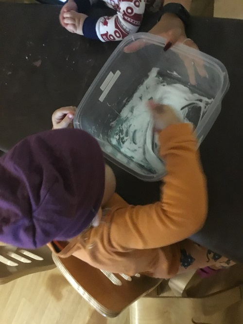 Toddler child mixes the slime with a spoon