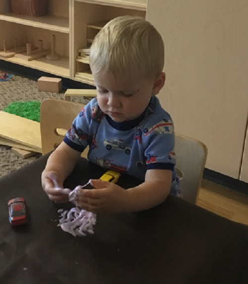Toddler boy touches the slime with his hands