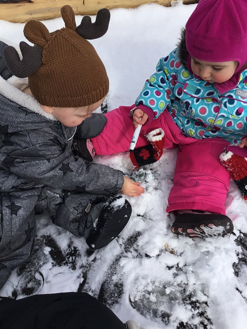 Infant boy and girl colouring in the snow with a marker
