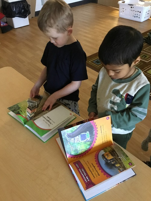 Two Preschool boys looking at a Train book