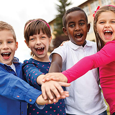 A stock photo of four school-aged children smiling widley while holding hands