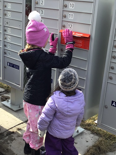 Child puts envelope in mail slot