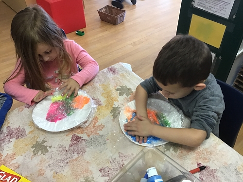 Two children work at hitting their plates full of paint