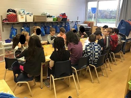 The entire group of children sits together for snack at a table