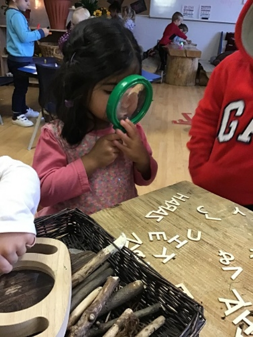 A child examines wooden letters using a magnifying glass