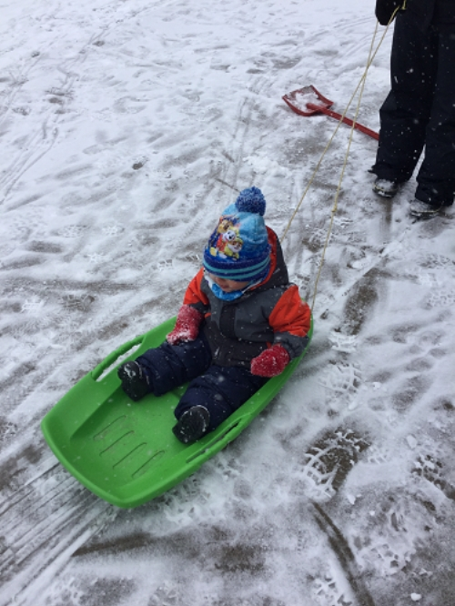 A child is pulled on a sled