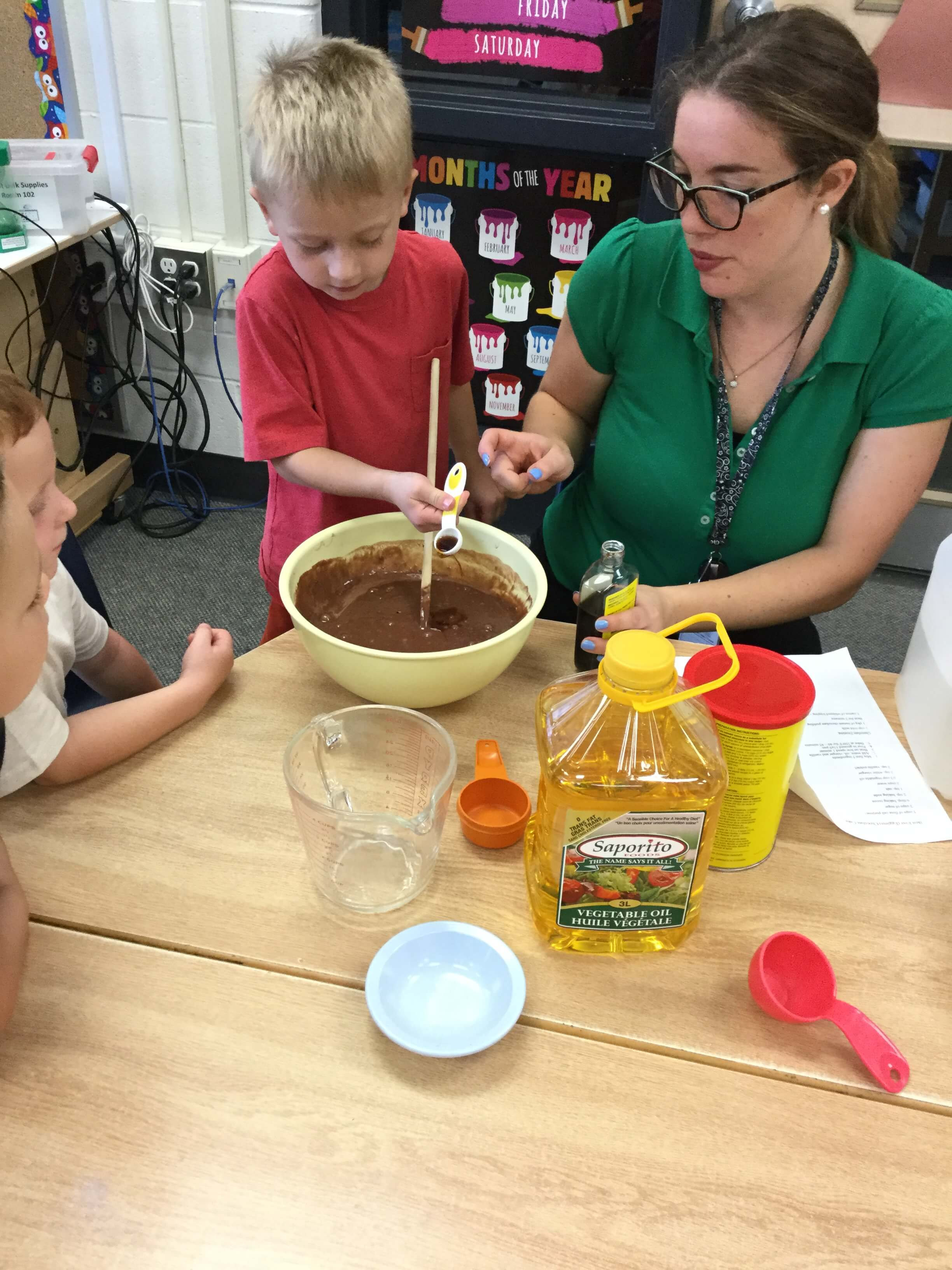 educator mixing batter with children
