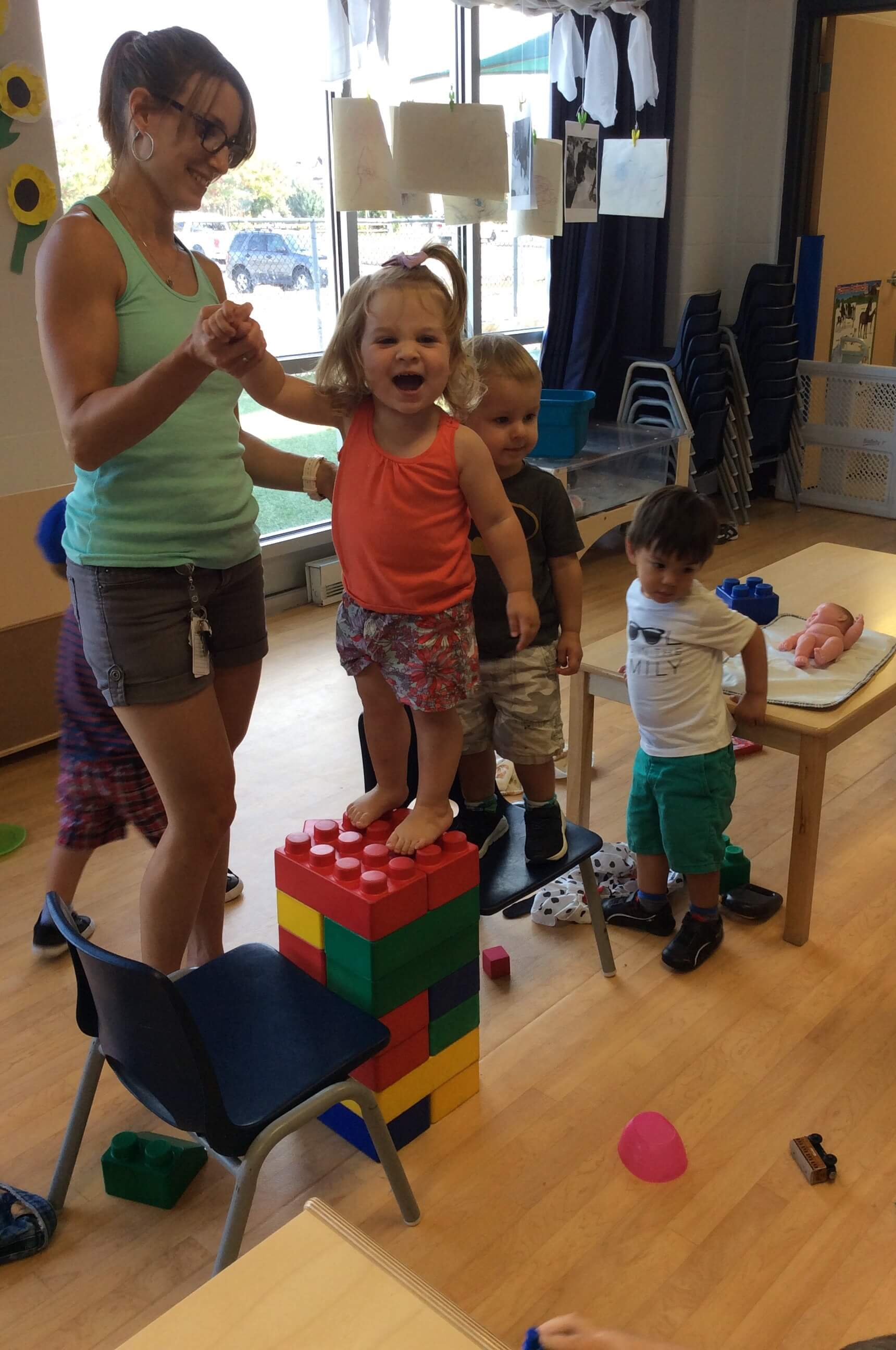 girl balancing on big lego blocks with educator