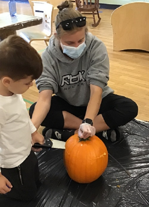 A female educator and preschool boy work together to saw the top off the pumpkin