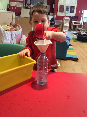 Boy pouring coloured water into funnel
