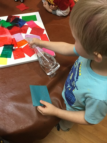 Boy spraying tissue paper with water