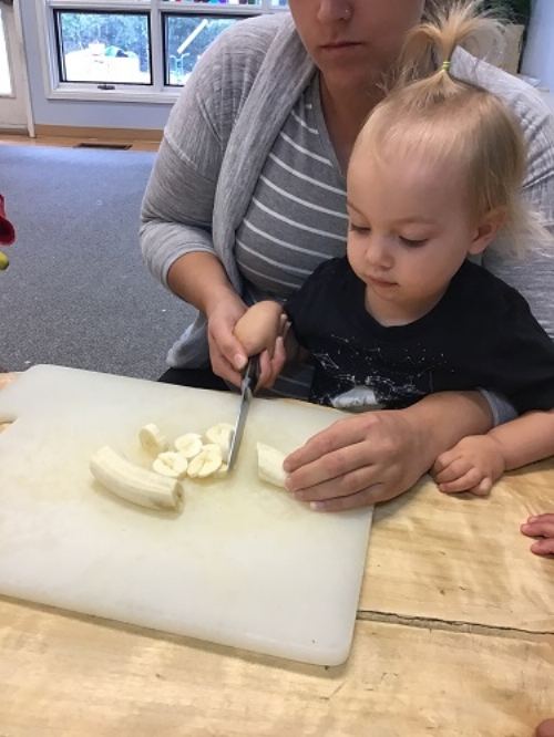 A toddler girl is helping a female educator cut fruit for fruit salad.