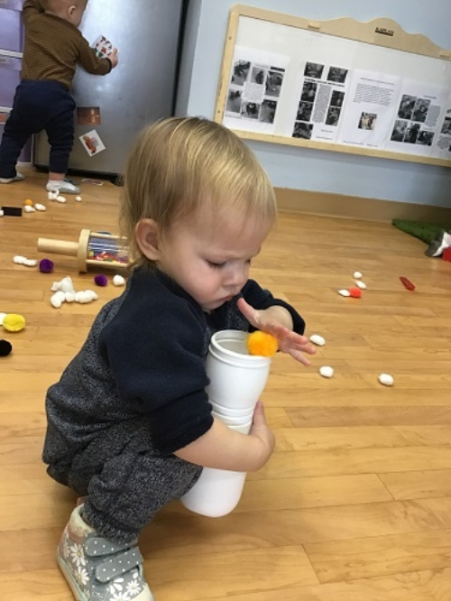 An infant girl is squating while holding a plastic chip container and placing pom poms into the container.