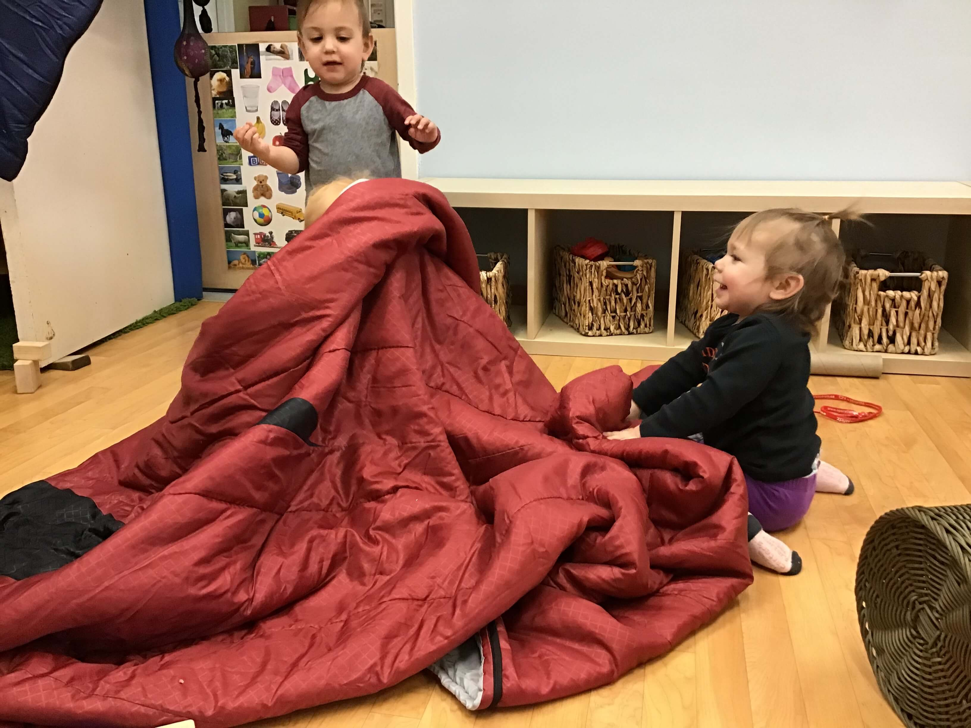 children hiding under a blanket