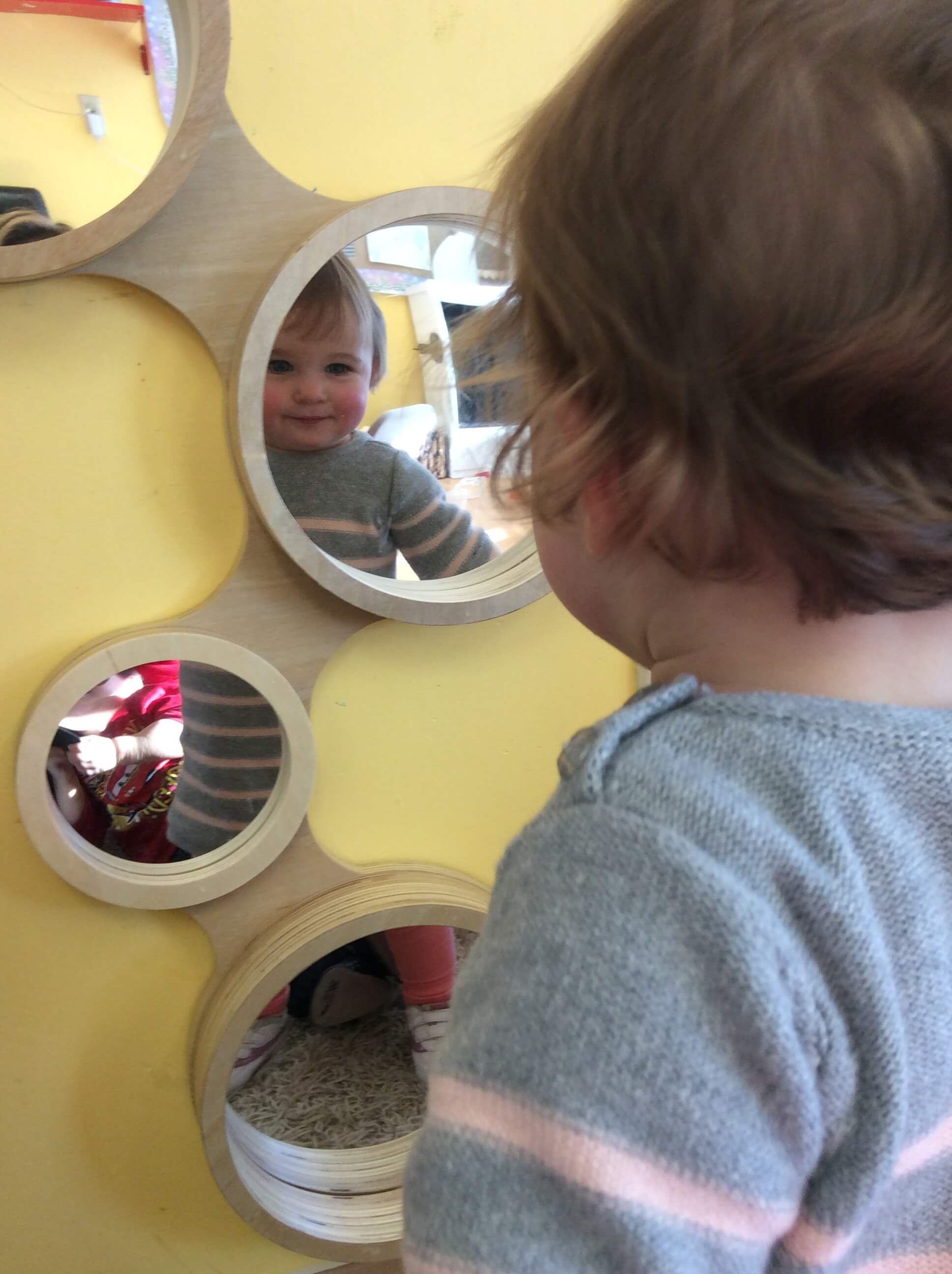 infant looking at her reflection