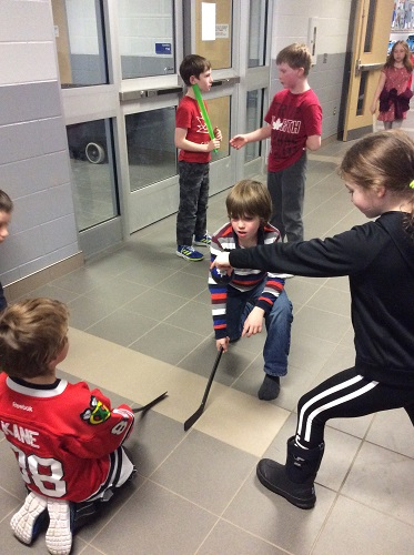 A group of chikdren play hockey