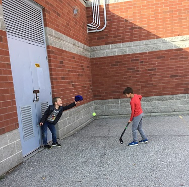 Two boys playing hockey outside