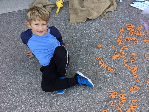 Boy making letters with playdough outside