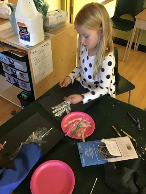 Girl using white paint to create a hand skelton painting