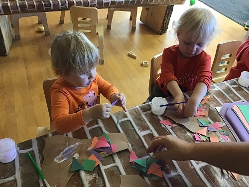 Two children sitting at a table gluing colourful paper