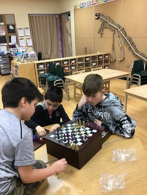Three boys sitting and playing chess