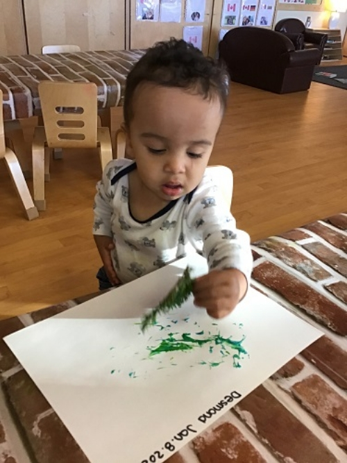A toddler painting with a branch