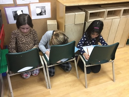 Three girls sitting on the floor using chairs as tables
