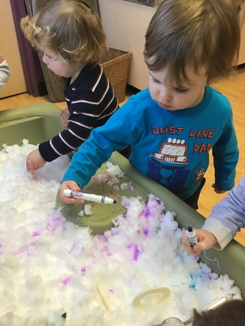 Two boys playing in a sensory bin full of snow