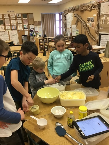 A small group of children gathered around a table mixing ingredients