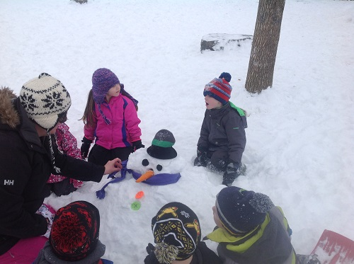 Children looking at the snowman they built