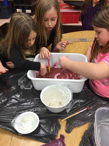 Group of children using their hands to explore kinetic sand