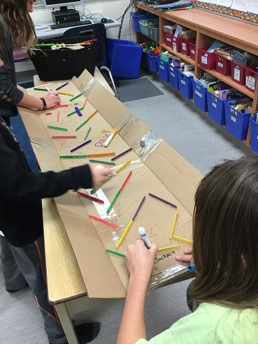 Group of children using markers to draw on cardboard marble run