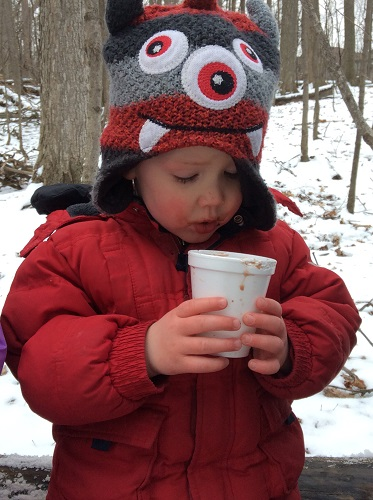 child looking in cup at hot chocolate