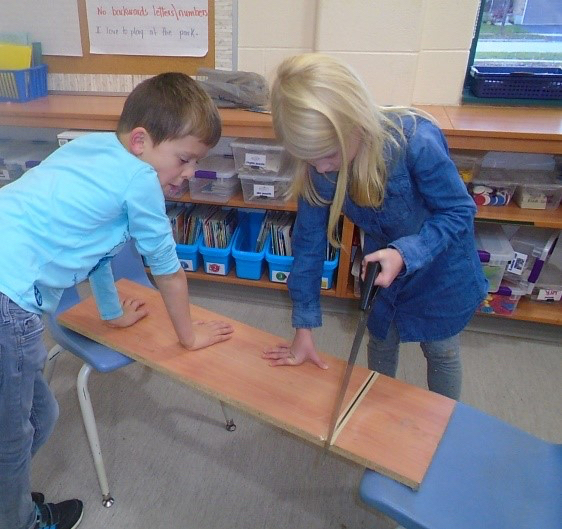 two children working together, one holding the board while the other child uses a saw to cut the board