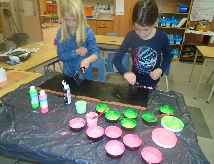 two children painting a board black
