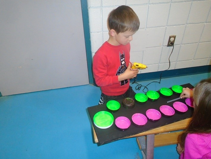 child using a glue gun to stick the bowls on the board