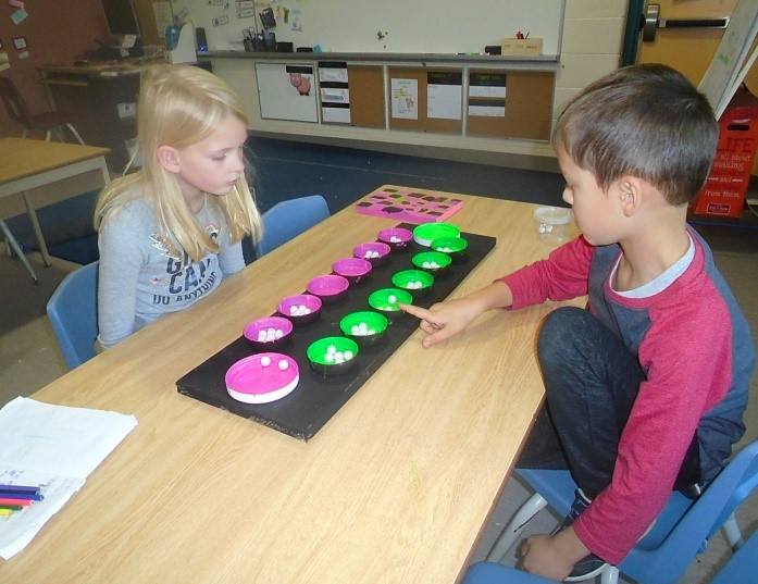two children sitting together playing Mancala