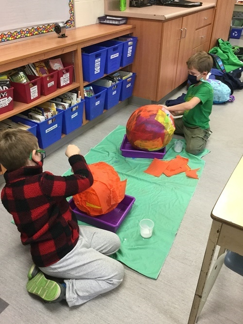2 boys putting paper mache on large balls