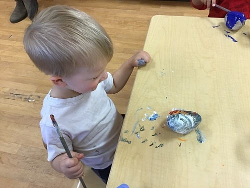 child painting his rock