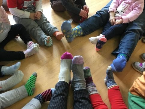 kids sitting in a circle showing off their socks