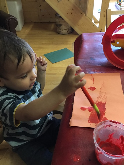 Child making marks with paint