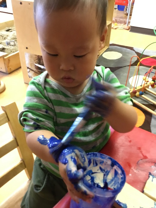 Child exploring paint with his hands