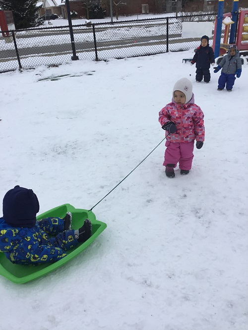 Child pulling another child in the sled outside in the playground