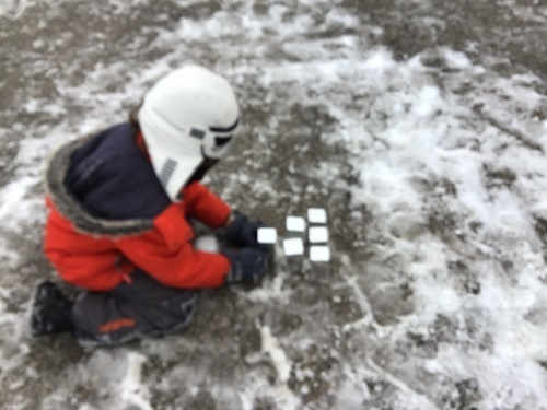School age child setting up blocks for snow bowling