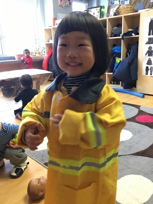 Child trying on a fire fighter jacket