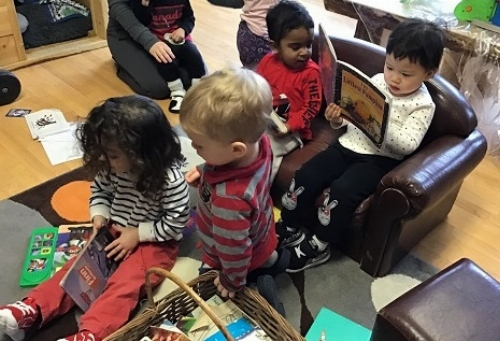Children looking at books in a cozy space