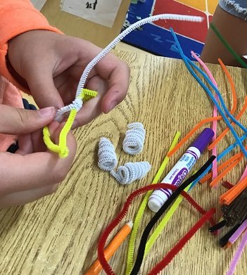 hand of school age child wrapping white pipe cleaner around yellow pipe cleanter