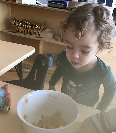 Child looking at pumpkin seeds in a bowl