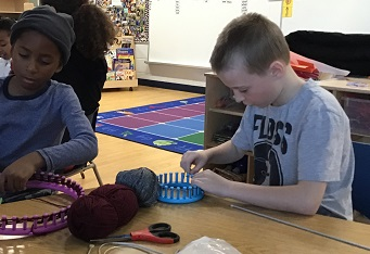 school age boy  using round knitting loom at a table with another boy